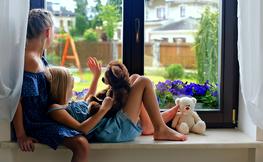2 nenes mirant per una finestra.