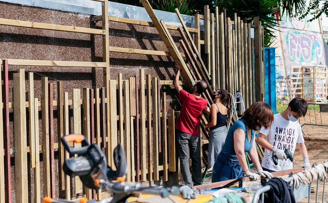 persones construïnt mur de fusta
